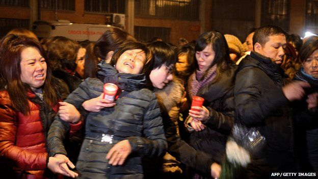 Chinese people cry and hold candles late on December 3, 2013 in Prato in homage to the seven victims of a Chinese-run garment factory fire