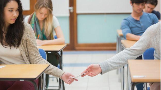 Dos jóvenes se pasan la respuesta de un examen a escondidas
