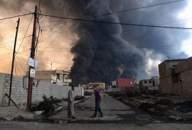 Hombres en la calle frente a un incendio provocado por la retirada de EI en Qayyarah, Irak