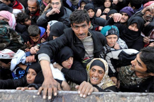 Ciudadanos sirios evacuados de Alepo intentan conseguir alimentos en una zona controlada por el gobierno.