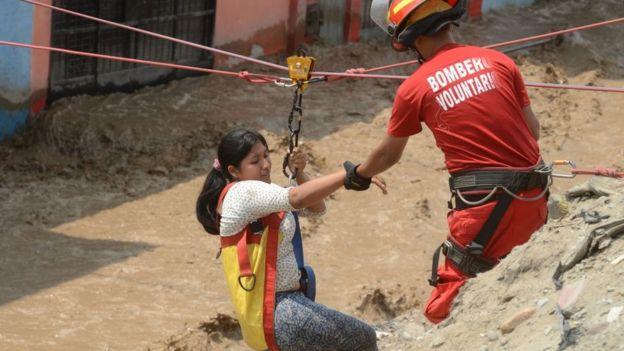 Bombero rescatando a una pobladora de Huachipa para que no se la lleve la corriente de un huaico.