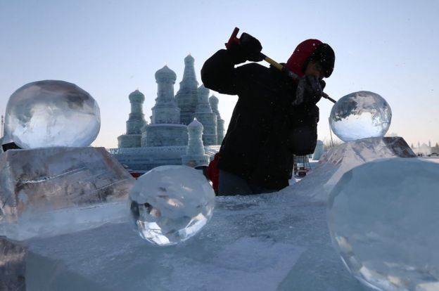 A worker carves an ice sculpture