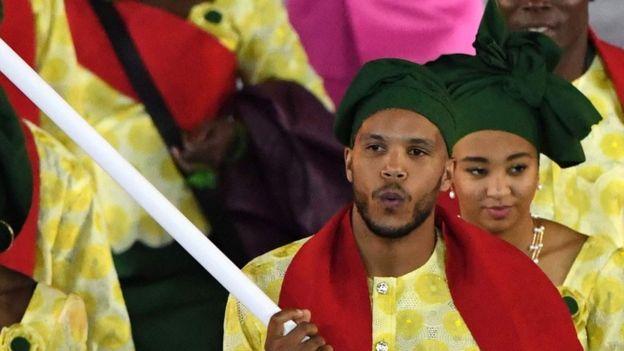 Yémi Apithy, esgrimista de Benín, llevando la bandera de su país en la ceremonia inaugural