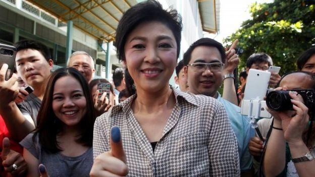 Former Thai Prime Minister Yingluck Shinawatra (center) shows her inked finger after casting her vote in Bangkok