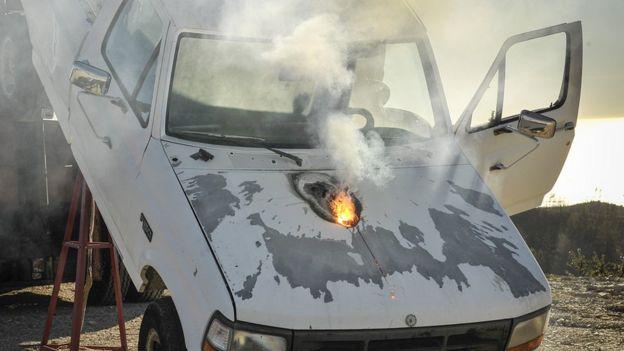 Fiery hole in bonnet of pick-up truck