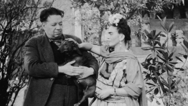 Mexican painters Frida Kahlo (1907 - 1954) and Diego Rivera (1886 - 1957) stand together with a pet dog in Mexico City, Mexico, in the 1940s.
