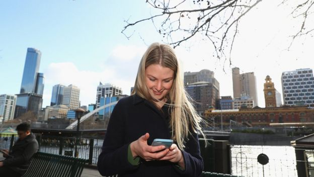 Mujer y hombre ven sus celulares y ni se prestan atención.