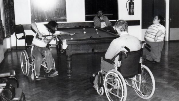 Four men, three wheelchair users and a man with dwarfism playing pool
