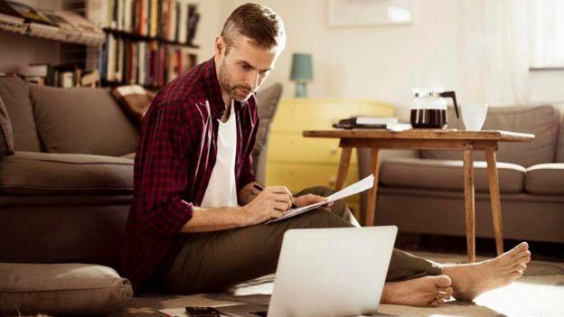 Un hombre con una laptop en la sala de su casa