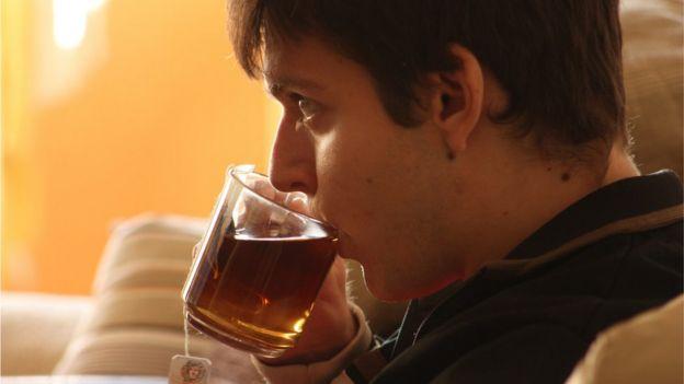 Joven tomando té en taza de vidrio