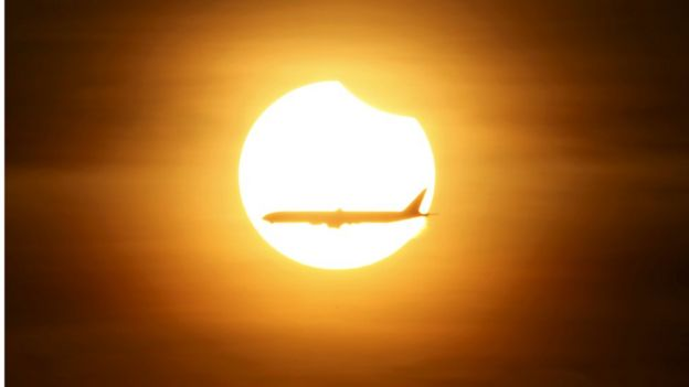 Plane flies across partial eclipse in Singapore