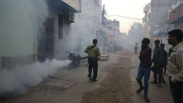 A municipal worker fumigates a residential area to prevent mosquitoes from breeding in Lucknow, India,