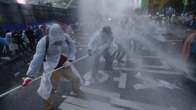 Protesters are sprayed with water cannons during the 14 November rally