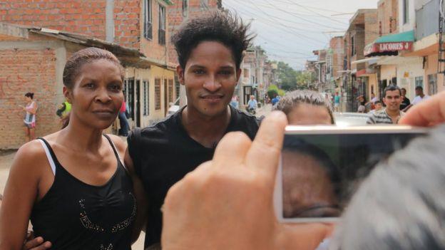 Una admiradora se toma una foto con Fernando Montaño en el barrio de Cali en el que creció el bailarín.