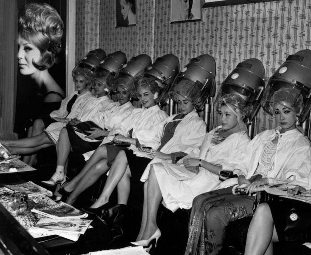 A group of Miss World contestants line up under the hairdryers at La Belle hairdressing salon in Aldwych, London