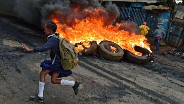 A schoolgirl runs past a burning barricade in Kibera slum, Nairobi, Kenya - Monday 23 May 2016