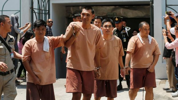 Four activists in handcuffs and prison uniforms, detained after posting critical comments on Facebook, leave a military court in Bangkok on 10 May 2016