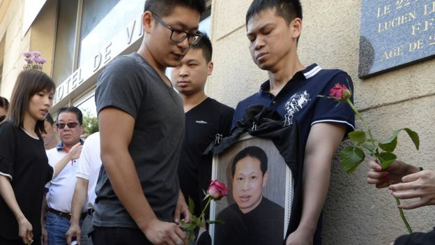 Family members and relatives hold a portrait of Chinese Zhang Chaolin as people light candles and lay flowers during a tribute ceremony, outside the city hall in Aubervilliers, north-eastern suburbs of Paris, on August 14, 2016.