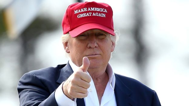 Donald Trump gives a thumbs up while wearing a Make America Great Again cap