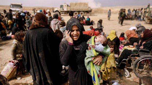 A displaced Iraqi woman talks on the phone as Iraqi forces battle with Islamic State militants in western Mosul, Iraq (27 February 2017)