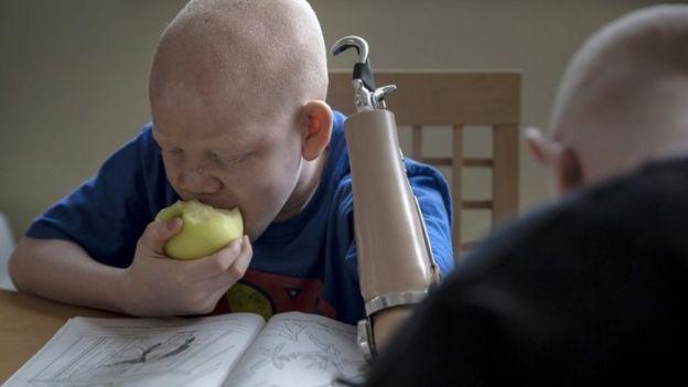 12-year-old Mwigulu Matonage from Tanzania eats an apple as he does homework in the Staten Island borough of New York, September 21, 2015