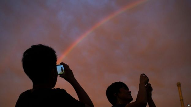Passersby take photos of a rainbow at sunset in Beijing on Monday, 3 August, 2015