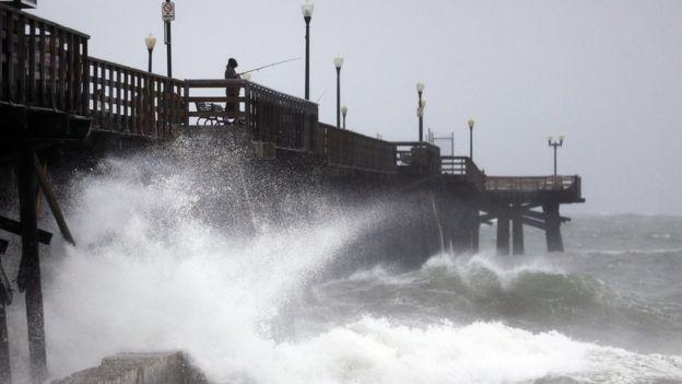 Waves crash against a pier in Seal Beach, California, on 17 February 2017