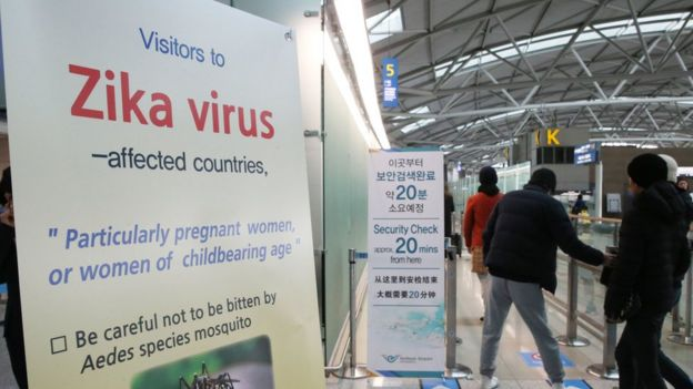 Passengers walk by a signboard about Zika virus at the passenger terminal of Incheon International Airport in Incheon, South Korea, Tuesday, March 22, 2016.