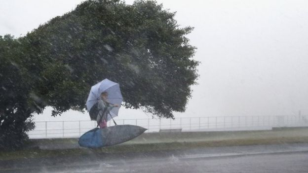 A young surfer leaves as a storm hits Bondi Beach on December 16, 2015 in Sydney, Australia