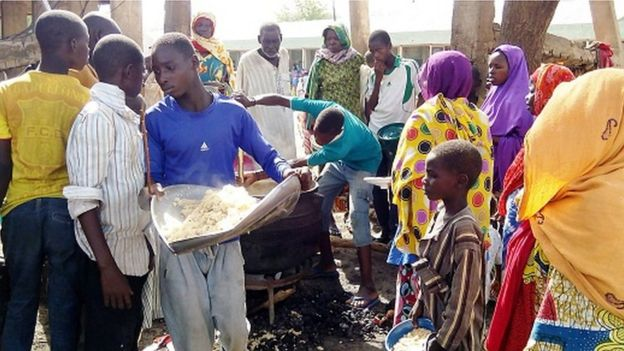 A man serves lunch from an open-air kitchen for people displaced by Boko Haram violence on May 19, 2016 in the Dalori Internally Displaced People's (IDP) Camp, near Maiduguri, northeast Nigeria.