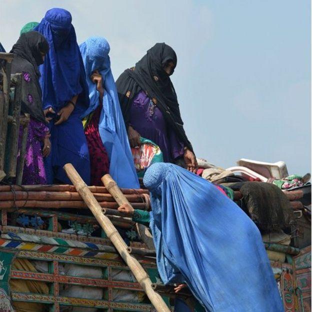 Mujeres afganas cubiertas con burkas intentan subir a un camión