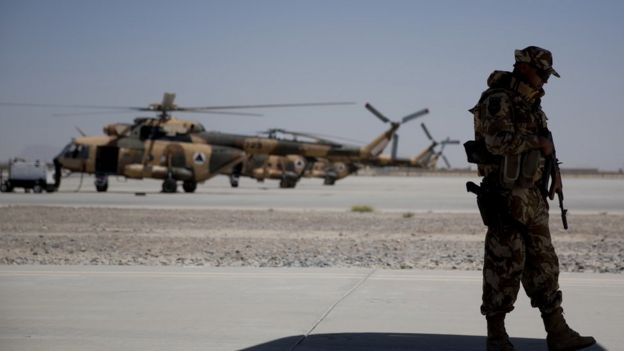 A Nato soldier stands guard under the wing of a C-130 Hercules aircraft that belongs to the Afghan National Army, in Kandahar Air Field, Afghanistan, Tuesday, Aug. 18, 2015