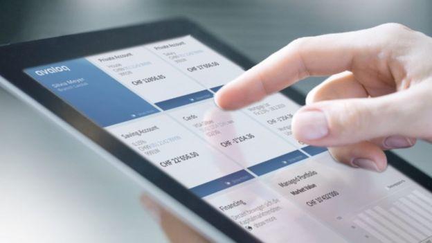Homem usa o programa da Avaloq num tablet