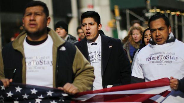 Jóvenes latinos marchan con una bandera de Estados Unidos en sus manos.