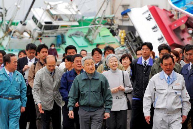 Akihito (centro) y la emperatriz Michiko (a su derecha) visitan los lugares devastados por el tsunami de 2011