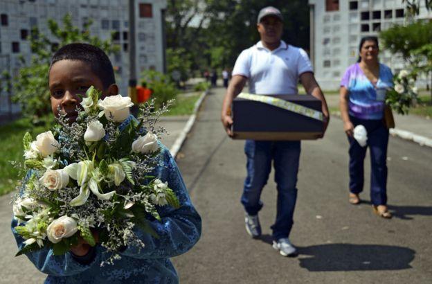 Niño carga un ramo de flores para un funeral