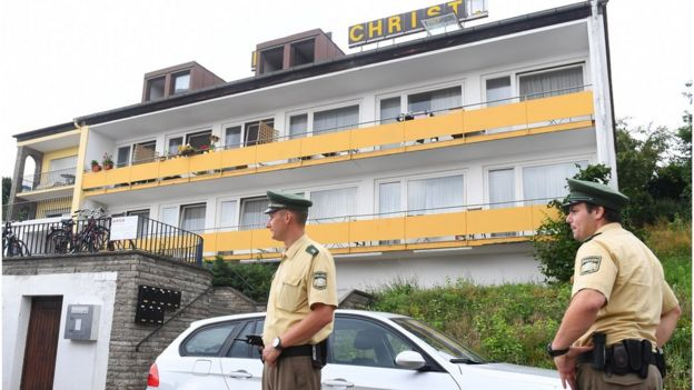 Police officers stand in front of a former hotel where a Syrian man lived before he blew himself up on Sunday at an open-air music festival in Ansbach (25 July 2016)