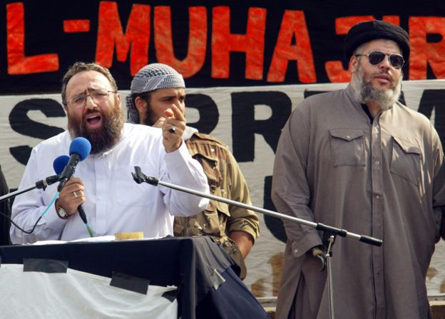 Sheikh Omar Bakri Muhammad (L) gestures while addressing devotees as fellow clergyman Sheikh Abu Hamza (R) waits his turn at the 'Rally for Islam' at Trafalgar Square in central London, 25 August 2002