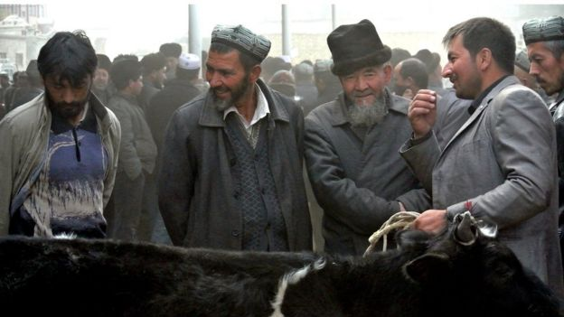 A picture taken on 7 November 2013 showing Uighur men gathering at a bazaar to sell their live sheep in Hotan, Xinjiang region.
