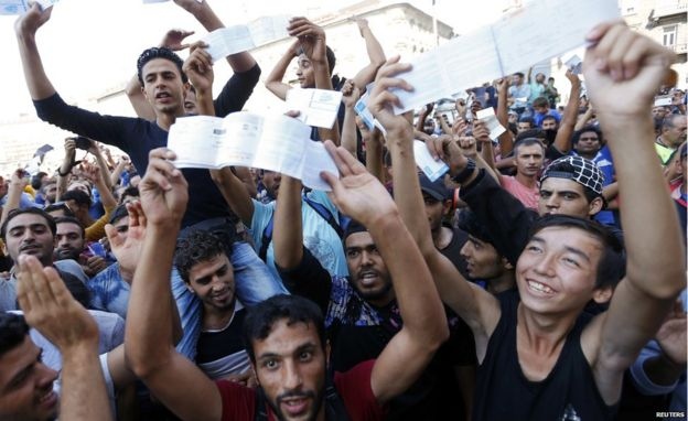 Migrants wave their train tickets outside the main Eastern Railway station in Budapest, Hungary, 1 September 2015