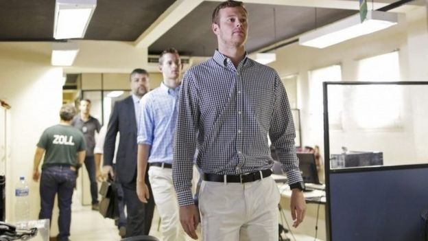 US swimmers Jack Conger and Gunnar Bentz are escorted into a police station the morning after they were stopped from boarding a flight to the United States, in Rio de Janeiro, August 18, 2016