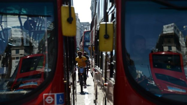 Ciclistas circulan entre dos autobuses en Londres.