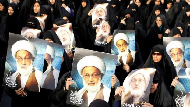 Protesters holding pictures of Sheikh Isa Qassim