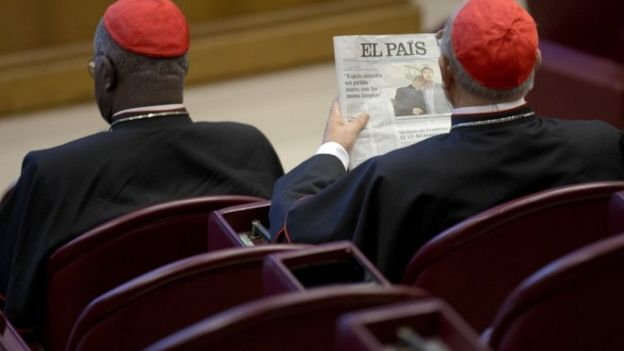 Spanish Cardinal Ricardo Blazquez Perez (right) reads a newspaper showing a picture of gay bishop Krzysztof Charamsa and his partner Eduard before the start of the morning session of the Synod of bishops on family issues at the Vatican (09 October 2015)
