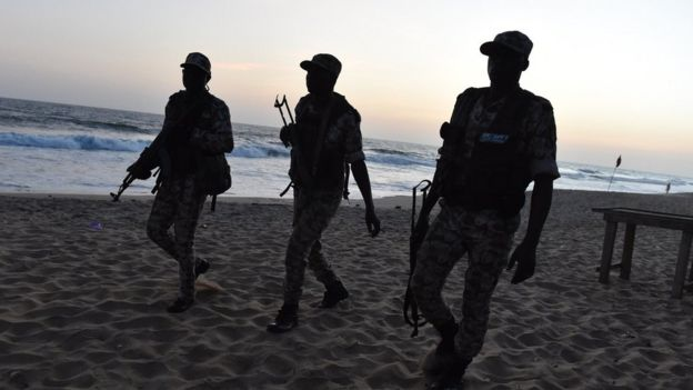 Ivorian soldiers walk on the beach after heavily armed gunmen opened fire on March 13, 2016 at a hotel in the Ivory Coast beach resort of Grand-Bassam