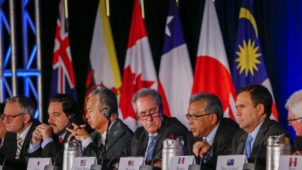 Reunión del TPP; con funcionarios sentados en el estrado con banderas de los respectivos países.