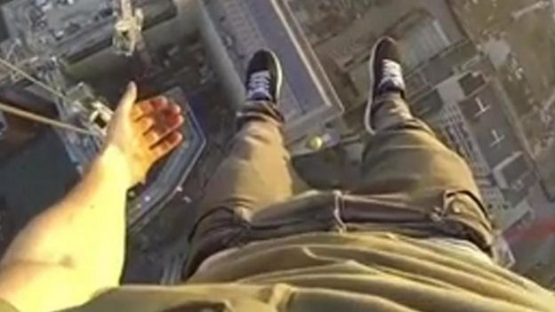 James Kingston hanging off a crane