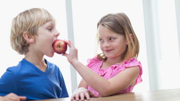 Niños comiendo una manzana