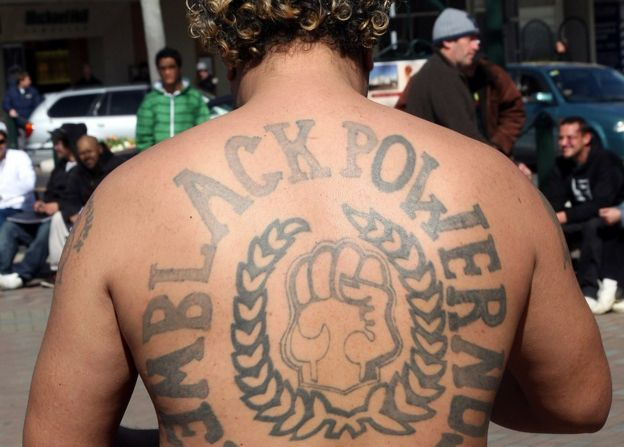 A Black Power Gang member shows his tattoo at a protest