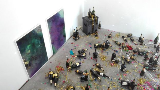 The artwork consists of empty champagne bottles, confetti and cigarette butts